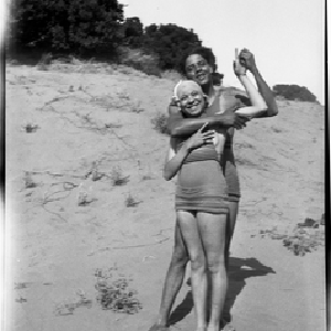 Young man and woman in swim suit embracing on beach