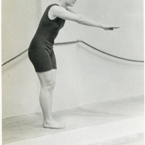 Young woman in a diving pose at the side of a pool