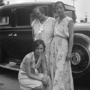 Three women standing next to automobile