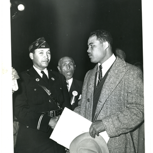 Joe Louis and unidentified man shaking hands, Frederick Roberts stands in the ...