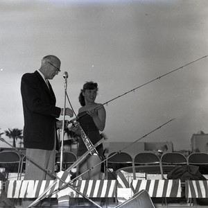 "Woman with ""Sportfisher"" ribbon sash on stage with fishing pole at unidentified ..."