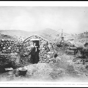 A desert miner standing in front of his stone cabin, near Randsburg, ...