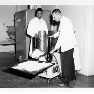 Howard Fifer working at drug manufacturing machine in lab with man in ...