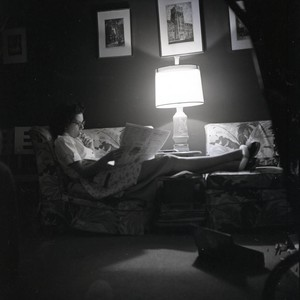 Woman on the couch reading a newspaper