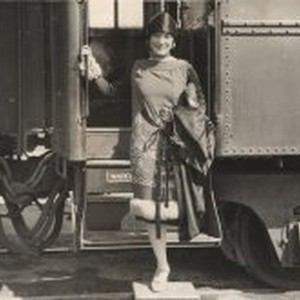 Finely dressed woman stepping off a train
