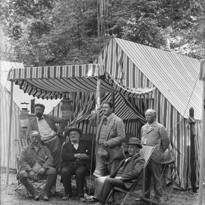 Group portrait of six men in front of striped tent, Bohemian Grove. ...