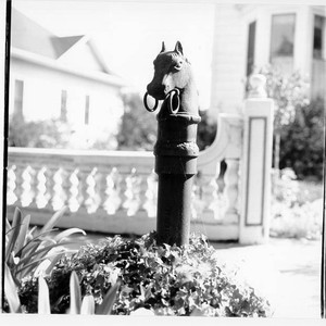 Iron hitching post in shape of a horse's head in front of ...