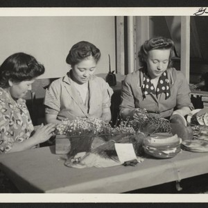 These three women, two of them Issei resettlers, are assembling artificial flower ...