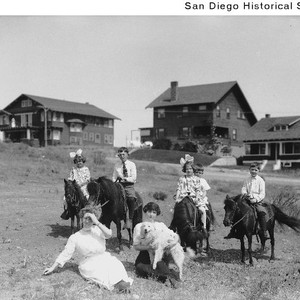 Children on ponies and two women with a dog in front of ...