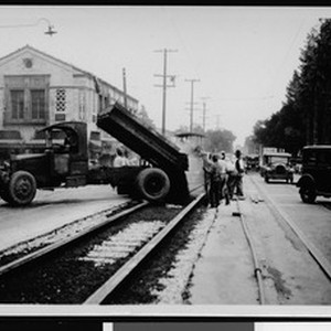 Asphalt being dumped between railroad tracks by dump truck