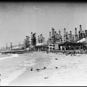 Children playing on the beach in front of an oil field, Playa ...