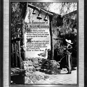 A photogrpah of a man standing on Olvera Street, reading a poster ...