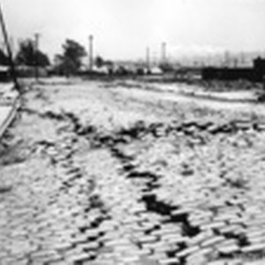 [Subsidence and fissures along street. Tents in distance (Columbia Square refugee camp?)]