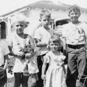 Calisphere: Cindy Watts poses with neighborhood kids, 1953