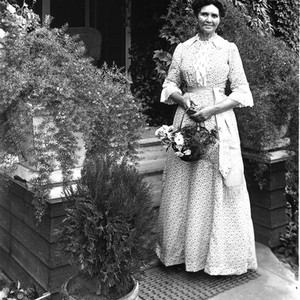 Portrait of a woman standing in front of a house, California: Photograph