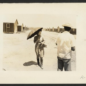 Poston, Ariz.--(Site #1)--This evacuee is fortified with an umbrella for protection from ...
