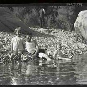 Three children at the edge of a river