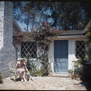 [Unidentified residential exteriors and landscaping]. Woman and dog