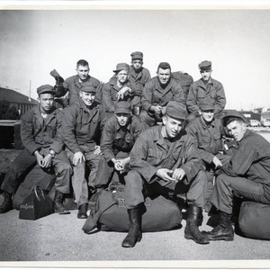 Trainees in informal group photo sitting on duffle bags at Fort Ord