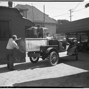 Men load a large crate into an automobile at a cooperative in ...